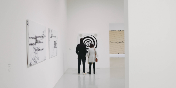 Two people standing in an art gallery, viewing a painting
